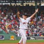 Carrying a trademark fungo bat, Johnny Pesky salutes the crowd on Sept. 28, 2008, when the Red Sox retired his No. 6 at Fenway Park.
