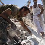 Syrians tried to reach the body of a man in the rubble of a building bombed by a Syrian warplane in Aleppo on Thursday.