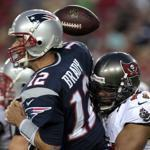 Tom Brady coughs up the ball while getting smacked by Michael Bennett.