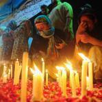 Relatives of fire victims held a candle vigil Thursday outside the garment factory in Karachi. Many victims were trapped.