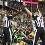 Officials seemed to indicate opposite reactions to the game-ending play in the Seahawks' win over the Packers. At left, the official appears to indicate an interception, while the official on the right called a touchdown.