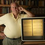 James Lynch next to a microfilm reader that is showing the 1708 freetown land transfer.