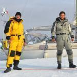 Morgan Peissel, Nicolas Peissel, and Edvin Buregren stand on the ice in the McClure Strait in front of their sailboat, the Belzebub II.