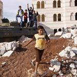 Children played on a destroyed Syrian government armored personnel carrier Monday in Azaz near the Turkish border.