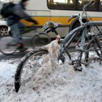 A bike is partly buried in snow while a cyclist shares the road with a bus on Commonwealth Ave.