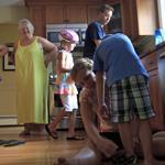 Jessica Wood ties son Emmett's shoes as her mother, Anne Low, looks on. Wood and her family live with her parents while they try to get out of debt. For now, buying even a used car (below) is a strain.