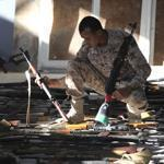 A Libyan soldier checked a room stocked with weapons handed in by militia.