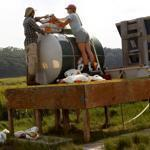 David Johnson and Kate Morkeski load a device that feeds fertilizer into the salt marsh on Plum Island.