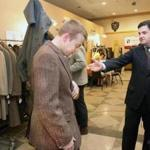 Joe Ferraro (right) helps Andrew Hanson-Dvoracek pick out a sports coat at Ferraro's flea market in Somerville.