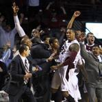 University of Massachusetts forward Sampson Carter (22)  sent fans into a frenzy after he hit a three pointer from the corner in front of his team's bench at the buzzer that broke a tie to give the Minutemen the victory against Harvard.