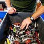 Tom Zekos of Newbury, N.H., searched tubs of confiscated pocket knives for sale at the surplus property store.