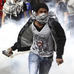 An anti-Morsi protester ran to throw back a tear gas canister during clashes with riot police in Cairo on Tuesday.