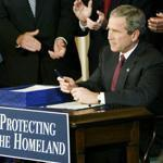 Surrounded by members of Congress, President Bush George W. Bush signs the Homeland Security Act on November 25, 2002.