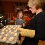 Amy Delaney and daughter Kate, 11, baked cookies for a holiday party. The family has tired of the shopping whirl.
