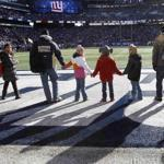 Students and families from Sandy Hook Elementary School in Newtown, Conn., stood on the field before the New York Giants game against the Philadelphia Eagles in East Rutherford, N.J., Sunday.
