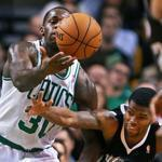 The Kings' Aaron Brooks does his best to beat Celtics forward Brandon Bass to the ball in first-half action.