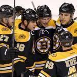 A huddle of happy Bruins means it must be a goal — and it is, a first-period strike by Tyler Seguin (center) that started a three-goal flurry.