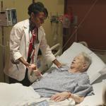 Boston University medical student Erica Perry checks on patient Alma Conroy at Boston Medical Center.