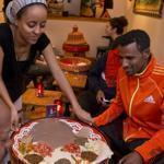 Waitress Tigist Kassa serves a taste of home to Ethiopian marathoner Gebre Gebremariam.