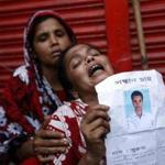 Mourners, carrying photos of missing relatives, have gathered near the collapsed building in Bangladesh.