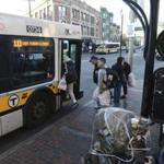 Passengers board Bus 111 at a stop in Chelsea. The bus links Chelsea and East Boston with South Station.