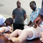 Harold Roy watched Joseph Bertrand (left) and Jean Ford Sainvil as they practiced cardiopulmonary resuscitation on baby mannequins in Port-au-Prince, Haiti.