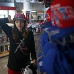 Michelle Downey tried on team caps at the New England Patriots Pro Shop in Foxborough earlier this month.