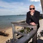 """John Waters, shown at his Provincetown home, writes about his three hitchhiking treks — two imagined and one real — in """"Carsick."""""""