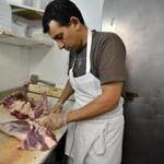 Al Bara Market's Laith Albehacy butchering a goat leg and rack of ribs.