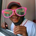 "Former Red Sox pitcher Pedro Martinez showed his good humor as he wore some big glasses given to him by a fan as he gave out Good Humor ice cream near the Copley T station as part of the team's ""Share the Love"" campaign."