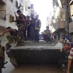 Syrian rebel fighters gathered around a former Syrian army tank Monday as they prepared to attack positions held by the government in an Aleppo neighborhood.