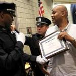Fabian J. Belgrave (left) realized his dream of becoming a police officer with the help of Boston police detective Larry Ellison (right), a man Belgrave considers a second father.