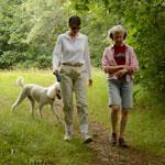 Laurie Bent (left) dressed in light clothing to avoid tick bites during a walk with Emily Hutcheson and Bent's dog.