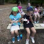 Kyla McNally, 9, enjoyed some gooey s'mores at a Girl Scout camp in Plymouth, where making s'mores is a long tradition.