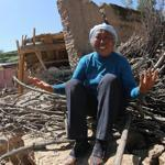 A resident cries on her collapsed house in Hetuo township in Dingxi, northwest China's Gansu.