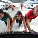 Alicia Drouin, Danette Gleason, and Sean Edmunds push an SUV during a workout with other Staples employees.