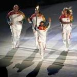 A procession of Russian Olympians relayed the torch to the cauldron, including Alina Kabaeva (front), Alexander Karelin (left), Elena Isinbaeva (center), and Maria Sharapova (right).EPA/ANATOLY MALTSEV