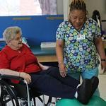 Mary McHale (left) was helped through therapy by certified nurse assistant Yva Cadet at Marian Manor, South Boston.