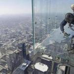 A worker replaced a layer of protective coating over the glass surface on the floor of one of four transparent ledges that jut out from the 103rd floor of the Willis Tower in Chicago.