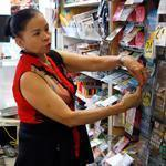 Teresa Nguyen gave a lottery ticket for a customer as she worked behind the counter at Tan-Thang Market on Broadway in Chelsea on Wednesday.