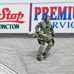 An Emergency Response Team member scaled a rooftop in Moncton, New Brunswick, during the search for a suspect.