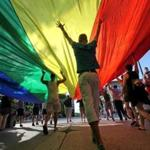 Supporters of a US Supreme Court ruling that overturned the federal Defense of Marriage Act carried a large rainbow flag during a parade around the Wisconsin State Capitol.