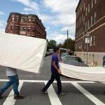 Students Avdit Kohli, Yan Olshevskyy, and Yajur Gulati carried mattresses down Commonwealth Avenue to their new apartment in Allston Monday.