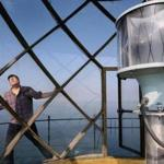 David Waller surveyed the lantern room, a glassed-in area atop the Graves Island Light Station, early this month. (Wendy Maeda/Globe Staff)