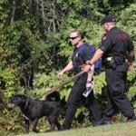 Detective Matt Denis of the Vermont State Police, left, and Trooper Charles Bergeron of the Rhode Island State Police and the search dog Zeus were in the woods near the Higgins Pool in Lawrence.