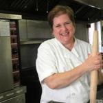 Melissa Lynch, rolling pin at the ready, in the Medford commercial kitchen where she makes her variety of savory and sweet hand pies.