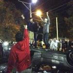 Light from a circling helicopter illuminated a group of young men jumping atop an overturned car in Keene on Saturday. The city's Pumpkin Festival goes back to 1991, but some wonder whether it has grown too big to con