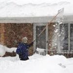 A man used a long fishing net to scrape snow off his roof just south of Buffalo, New York.