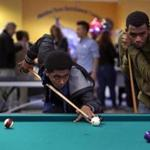 Nathan Ghebrem-icael lines up a shot as Joshua Monteiro, 17, looks on at the Malden Teen Enrichment Center.