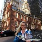 "Denise D. Price holding her ""Freedom Trail Pop Up Book of Boston"" in front of the Old State House in Boston."